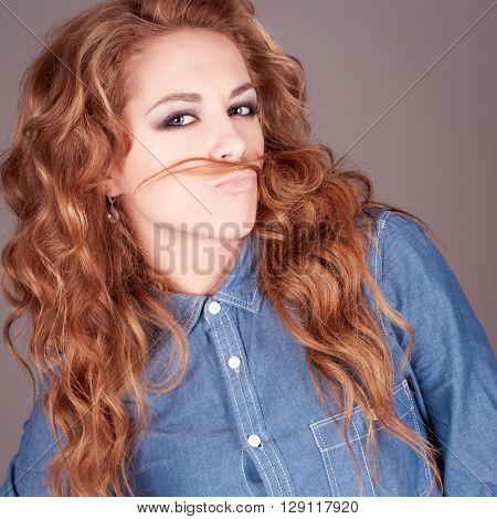 Beautiful young girl having fun in room over grey. Making mustache with hair. Wearing denim shirt.