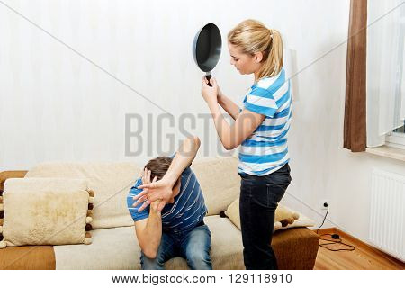 Angry young woman trying hit her husband with pan