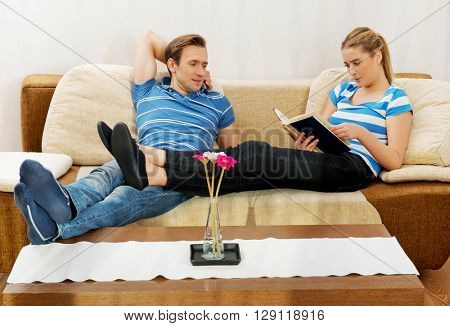 Woman reading a book while her husband is watching TV in living room