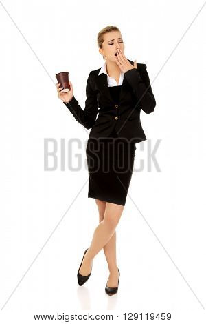 Tired yawning business woman holding a paper cup of coffee