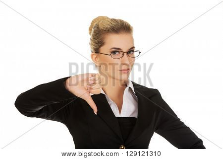 Unhappy young businesswoman with thumbs up