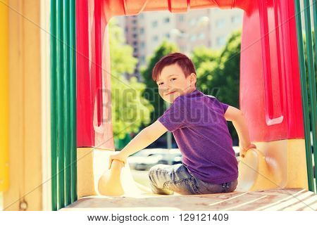 summer, childhood, leisure and people concept - happy little boy on slide at children playground