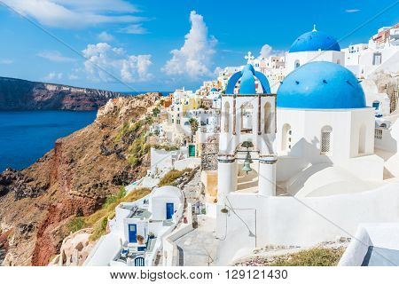Greece famous touristic travel destination Santorini greek island. Three blue domes. Popular summer luxury vacation Europe cruise stop. Streets of European white village with the mediterranean sea.