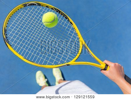 Tennis player holding yellow ball on racket grid. Sports female athlete taking a feet selfie showing running shoes on blue hard court. POV closeup of equipment, neon yellow fashion footwear.
