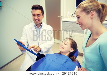 people, medicine, stomatology, technology and health care concept - happy male dentist showing tablet pc computer to patient girl and her mother at dental clinic office