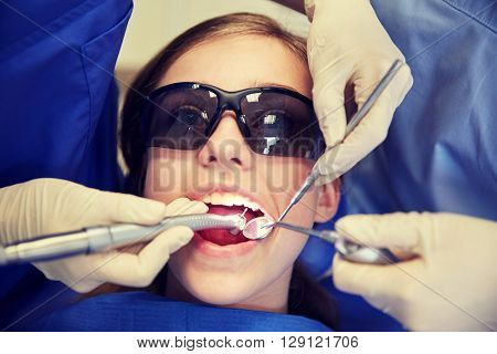 people, medicine, stomatology and health care concept - female dentists with mirror, drill and probe treating patient girl teeth at dental clinic office