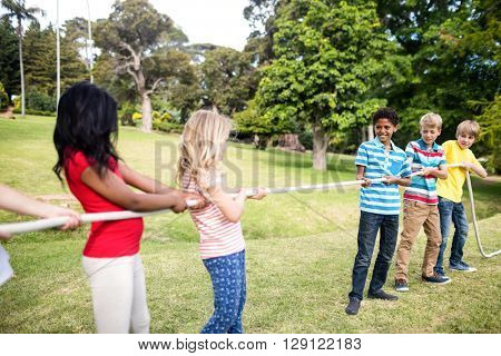 Children pulling a rope in tug of war in the park