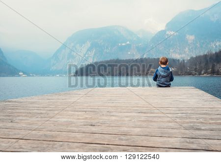 Little boy sits on the wooden pier near the blue mountain lake ObertraunAustria