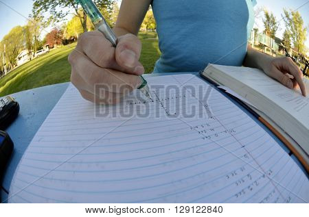 Child doing homework writing on paper with pencil