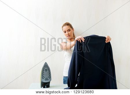 Young woman ironig man's jacket on ironing board