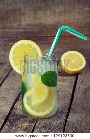 Cold lemonade with ice. Detox cocktail. Refreshing homemade lemon and mint cocktail over old vintage wooden table. Detox fruit infused flavored water