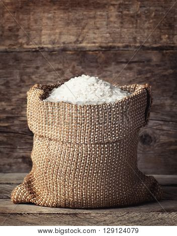 raw white rice in burlap sack on wooden background. Filling bag with rice. White rice on wooden background. Grains of rice in bag