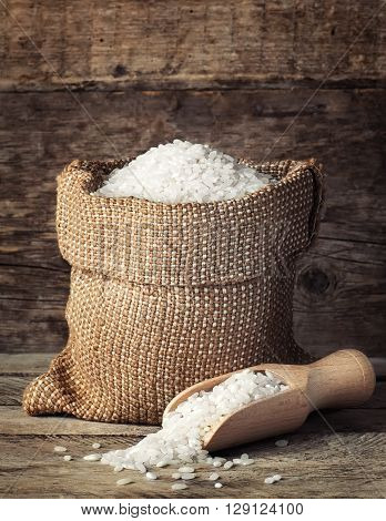 raw white rice in burlap bag with scoop on wooden background. Filling bag with rice. White rice on wooden background