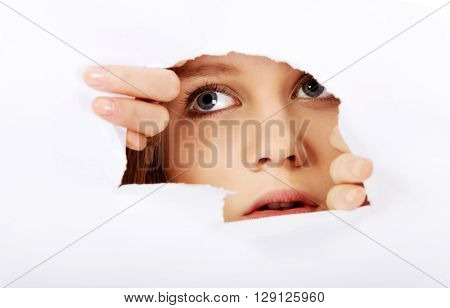 Teenage woman peeping through hole on paper