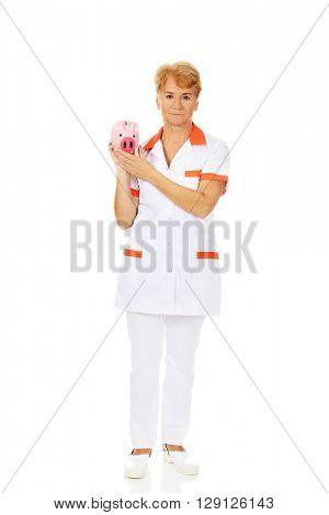 Smile elderly female doctor or nurse holding piggybank