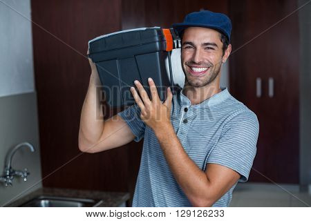 Portrait of smiling man carrying toolbox while standing in kitchen