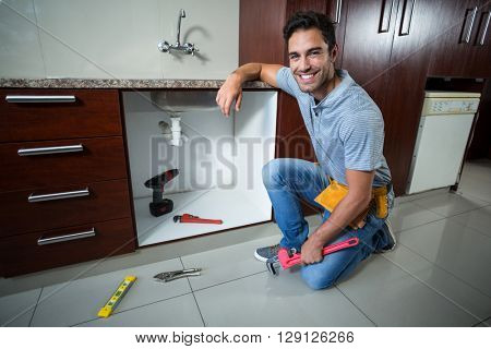 Portrait of smiling man holding pipe wrench in kitchen