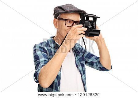 Studio shot of a senior photographer shooting with a retro camera isolated on white background