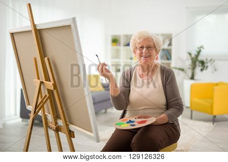 Elderly woman painting on a canvas seated on a chair at home
