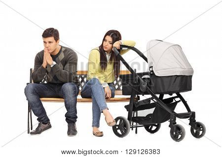 Worried young mother and father sitting on a bench and contemplating isolated on white background