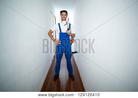 Portrait of confident pesticide worker standing in hallway at home
