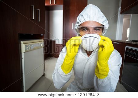 Portrait of confident pesticide worker wearing mask in kitchen at home