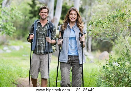 Portrait of happy hikers walking with poles in forest