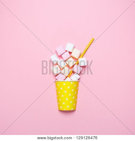 Top view of the pastel marshmallows on a pink background.