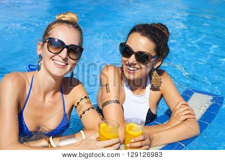 Beautiful young women drinking a cocktails while relaxing in the swimming pool