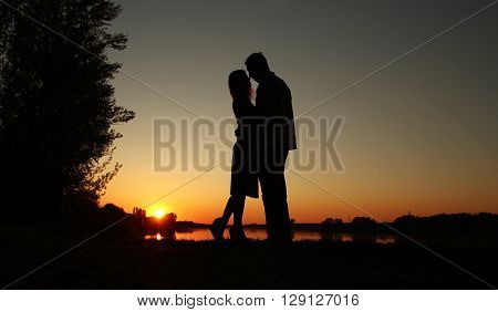 a silhouette of a couple in love at sunset