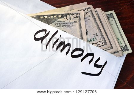 Alimony written on an envelope with dollars.
