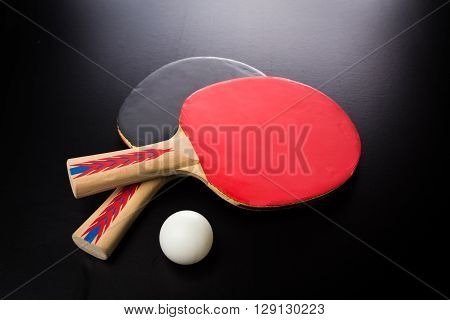 tabletennis racket and ball on black table