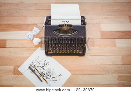 The word sorry and brainstorm graphic against typewriter and paper on table in office