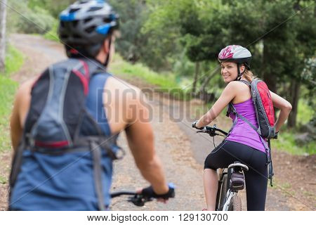 Cheerful female happy biker looking at man on footpath in forest