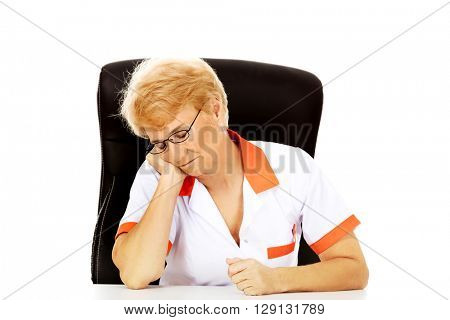 Tired elderly female doctor or nurse sleep with head on hand