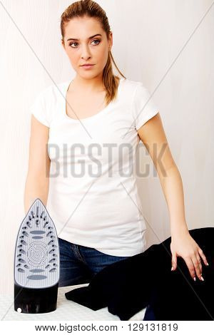 Happy young woman ironing on ironing board