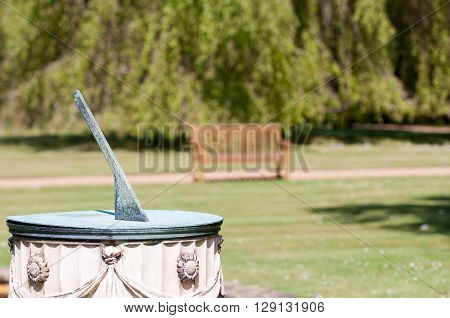 Sundial in the grounds of a garden in bright sunlight