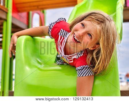 Child girl upside down on park playground game. Slippery dip girl.