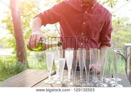 man pouring a bottle champagne in flutes glasses