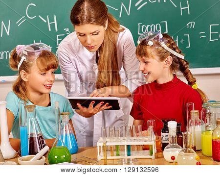 Children and teacher holding flask in chemistry class. Looking at pc. Studying chemistry at school.