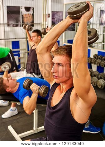 Group of men working on simulator his body at gym. Strong man with dumbbells on foreground into gym.