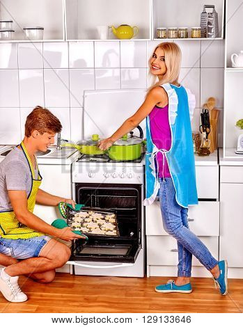 Young family man and woman baking cookies in oven. Baking at home.