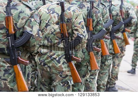 Sofia, Bulgaria - May 4, 2016: Soldiers from the Bulgarian army are preparing for a parade for Army's day in uniforms with Kalashnikov AK 47 rifles. Seen from thei backs. Unrecognisable people.