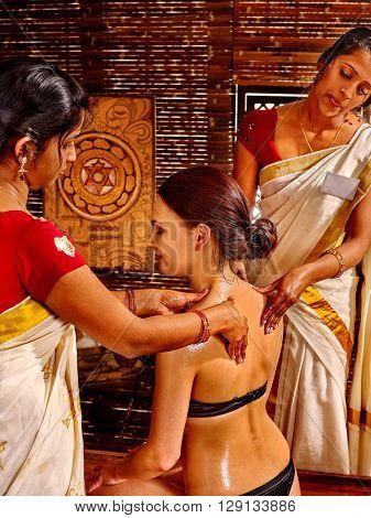 Woman having Ayurvedic spa massage treatment. Pouring oil massage.