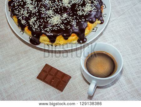Cheesecake with chocolate glaze and sesame, bar of milk chocolate and  coffee in a white cup on the table