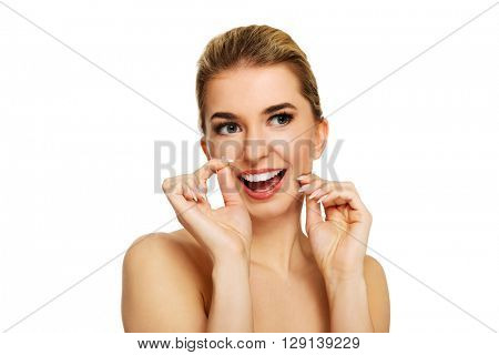 Young woman flossing teeth.