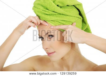 Woman checking wrinkles on her forehead.