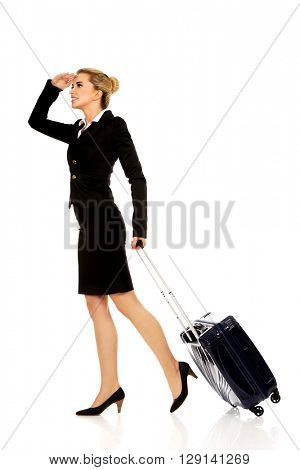 Businesswoman with wheeled suitcase covering eyes with hand