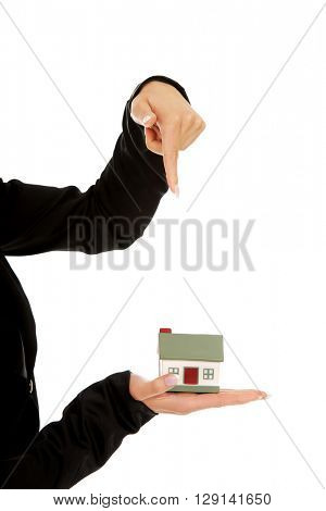 Businesswoman pointing on a model house in hand