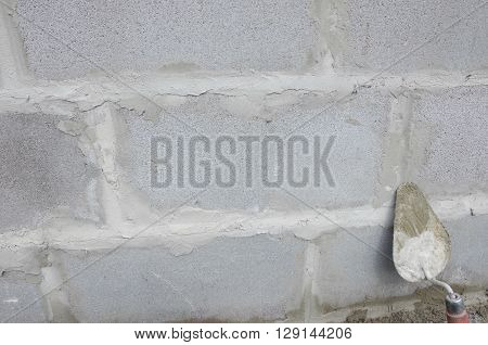 Trowel on cinderblock gray background. against the background of the brickwork is trowel